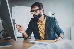工作在台式计算机上的晴朗的办公室的年轻有胡子的人,当坐在木桌上时 商人分析股票 免版税图库摄影