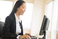 工作在台式计算机的惊奇的女实业家 免版税图库摄影