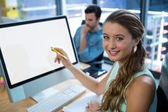 工作在台式计算机的美丽的妇女在办公室 免版税库存图片
