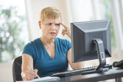 工作在台式计算机的被拉紧的女实业家 免版税库存照片