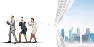 工作在合作和拉扯白色广告横幅的年轻买卖人 免版税库存图片