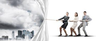 工作在合作和拉扯白色广告横幅的年轻买卖人 库存图片