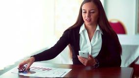 工作在咖啡有文件的女商人商店 坐与在咖啡馆的片剂的少女 严重的妇女年轻人 股票录像