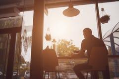 工作在咖啡馆的一个人的剪影 免版税库存图片