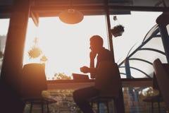 工作在咖啡馆的一个人的剪影 免版税图库摄影