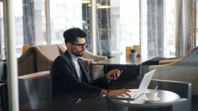 工作在咖啡馆的企业主使用膝上型计算机和智能手机现代小配件 影视素材