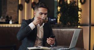 工作在咖啡馆的年轻商人 使用智能手机和膝上型计算机的自由职业者 成功的事务,IT,自由职业者概念 股票视频