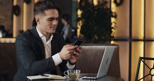 工作在咖啡馆的年轻商人 使用智能手机和膝上型计算机的自由职业者 成功的事务,IT,自由职业者概念 股票录像