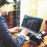 工作在咖啡馆的年轻人摄影师,使用膝上型计算机 免版税库存照片