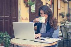 工作在咖啡馆,饮用的咖啡的年轻女商人 免版税库存图片