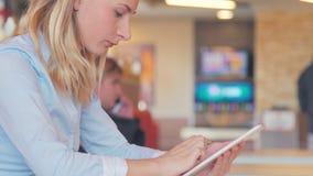 工作在咖啡馆 坐在桌上和使用片剂的年轻美丽的长的头发妇女 股票录像