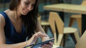 工作在咖啡馆 坐在桌上和使用片剂计算机的年轻美丽的长的头发妇女在室外咖啡馆 库存图片