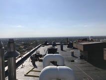工作在商业大厦,屋顶项目的一个光滑的修改过的屋顶平台的盖屋顶的人 免版税库存照片