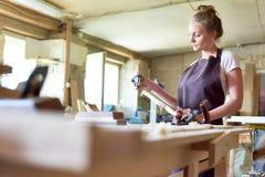 工作在商店的女性木匠 免版税库存图片