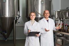 工作在啤酒厂的男人和妇女 免版税库存照片
