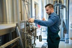工作在啤酒厂的酿酒者 免版税库存照片