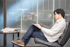 工作在图书馆里的年轻亚裔人大学生 免版税库存图片