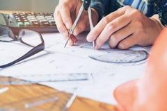 工作在图纸的办公室的建筑师或工程师 建筑师 图库摄影