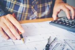 工作在图纸的办公室的建筑师或工程师 建筑师 免版税图库摄影