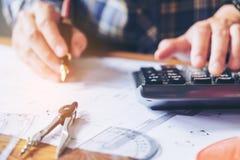 工作在图纸的办公室的建筑师或工程师 建筑师 免版税库存图片
