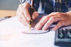 工作在图纸的办公室的建筑师或工程师 建筑师 免版税库存照片