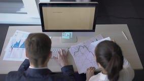 工作在图纸的年轻成功的买卖人,坐在与计算机4k,男人和妇女谈论的桌上 影视素材