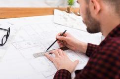 工作在图纸的建筑师在办公室 免版税图库摄影