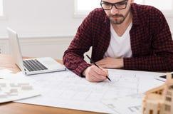 工作在图纸的建筑师在办公室 免版税库存图片