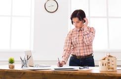 工作在图纸的建筑师在办公室 库存照片