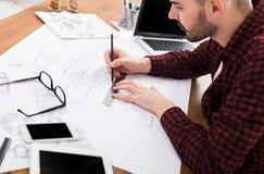 工作在图纸的建筑师在办公室 免版税库存照片