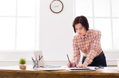 工作在图纸的建筑师在办公室 图库摄影