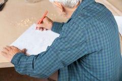 工作在图纸的资深建筑师在表上 图库摄影