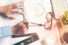 工作在图纸的顶视图建筑师 建筑师工作场所 设计工具和安全控制,图纸,统治者,橙色舵 免版税库存照片