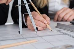 工作在图纸的建筑师在书桌在办公室 图库摄影