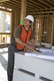 工作在图纸的建筑师在站点 免版税图库摄影