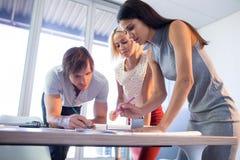 工作在图纸的建筑师在他们的书桌 图库摄影