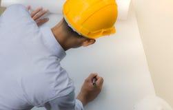 工作在图纸的建筑师 工程师审查员在工作场所 免版税图库摄影
