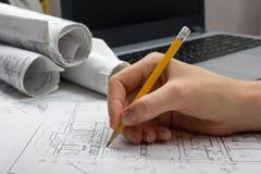 工作在图纸的建筑师 建筑师工作场所-建筑项目,图纸,统治者,计算器,膝上型计算机和 库存照片