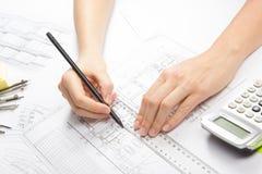工作在图纸的建筑师 建筑师工作场所-建筑项目,图纸,统治者,计算器,膝上型计算机和 库存图片