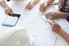 工作在图纸,工程师会议的建筑师与pa一起使用 免版税库存照片