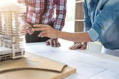 工作在图纸,工程师会议的建筑师与pa一起使用 免版税图库摄影