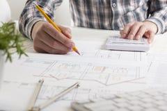工作在图纸,房地产项目的建筑师 建筑师工作场所-建筑项目,图纸,统治者 免版税图库摄影