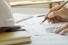 工作在图纸,建筑概念的建筑师或工程师 库存图片