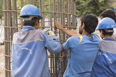 工作在圆柱形金属结构的建筑工人 库存照片