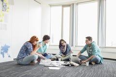 工作在地板上的买卖人在创造性的工作区 图库摄影