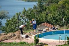 工作在地面游泳池的人 库存照片