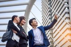 工作在城市的企业队,看一个手机 图库摄影
