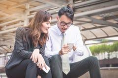 工作在城市的企业队,看一个手机 免版税图库摄影