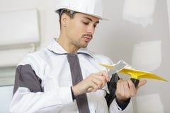 工作在墙壁上的年轻人石膏工在楼房建筑 免版税库存照片