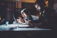 工作在夜办公室的有胡子的年轻工友 使用当代膝上型计算机和现代智能手机的人 水平 蠢材 免版税库存照片
